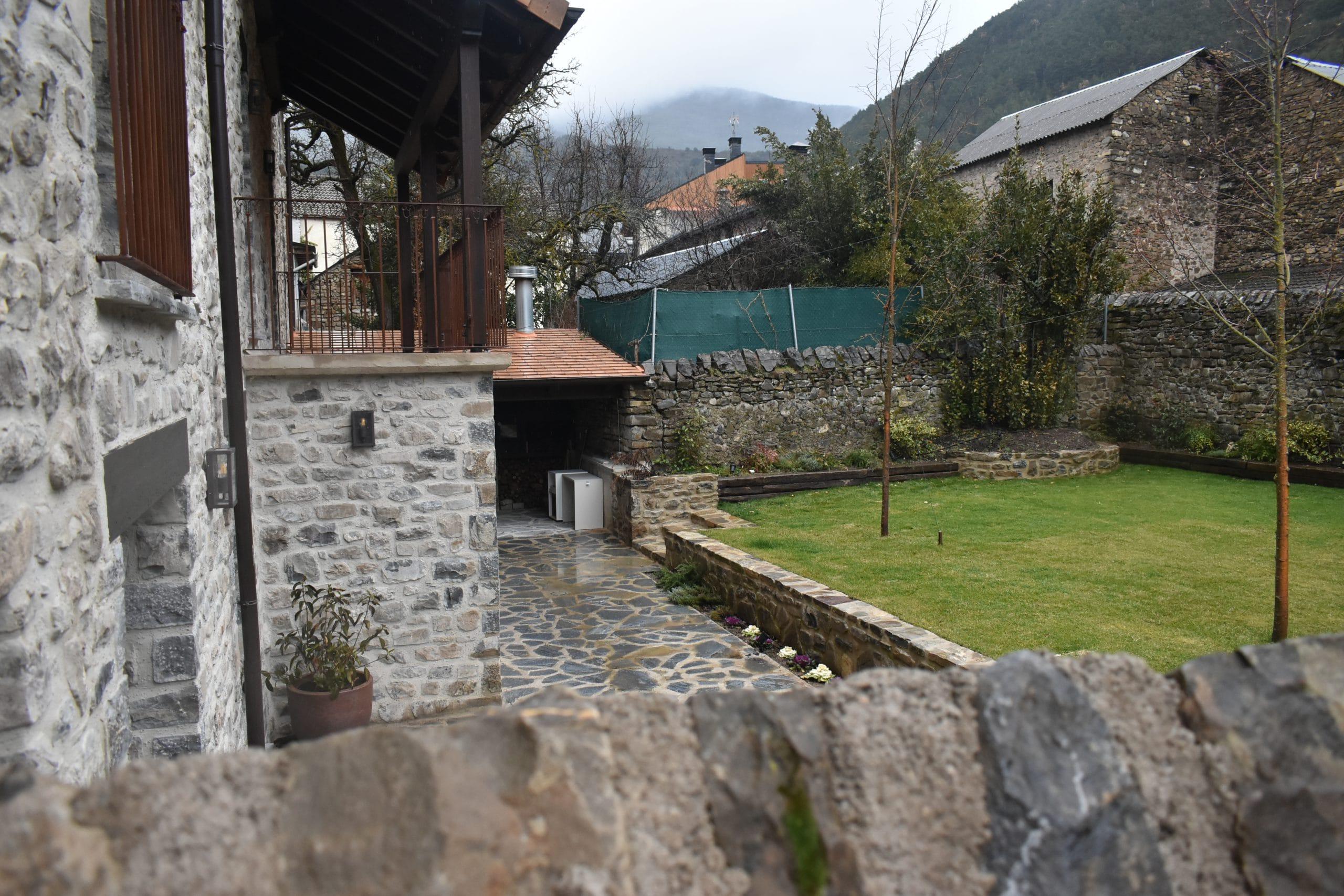 Casa rústica con jardín y parterres