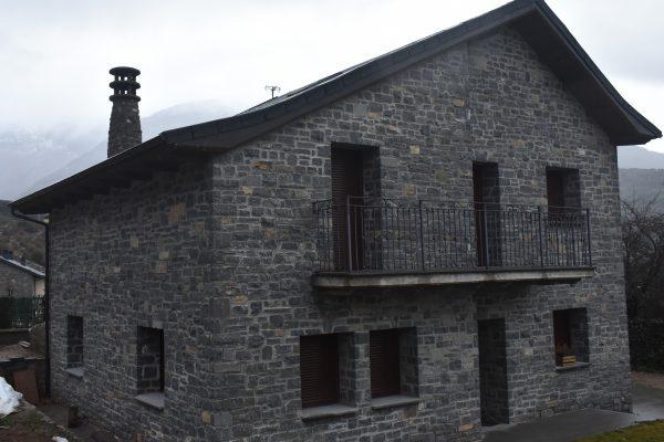 Casa rústica de dos plantas con fachada de piedra