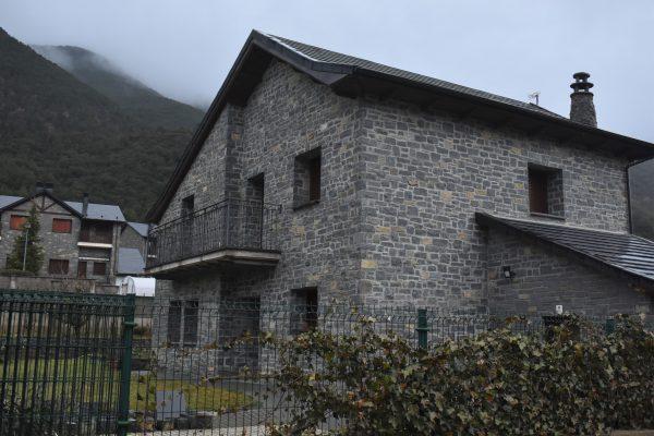 Casa rústica de dos plantas con fachada de piedra con vista del jardín
