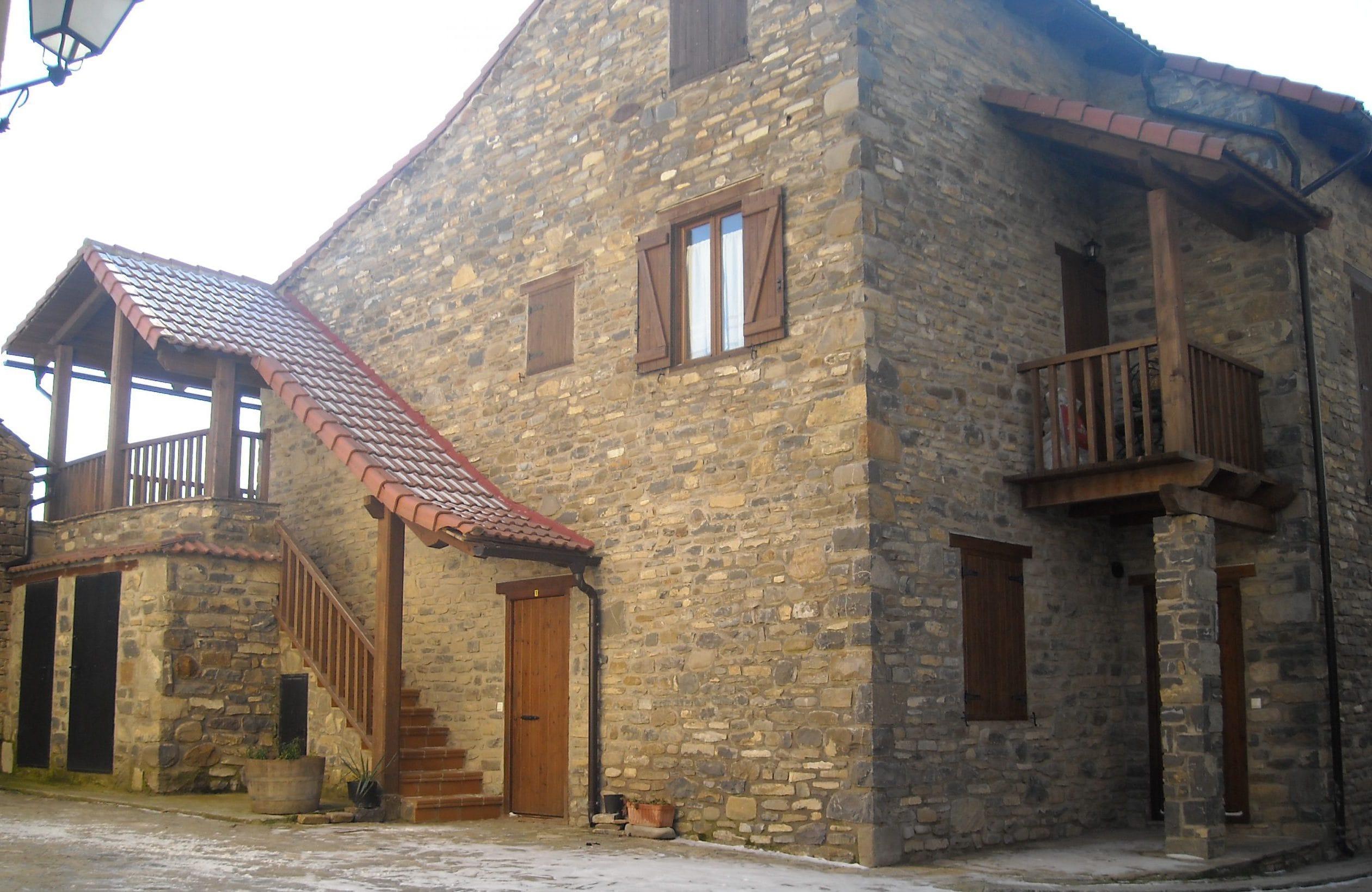 Edificio de apartamentos de obra rústica con fachada de piedra vista y balconadas de madera